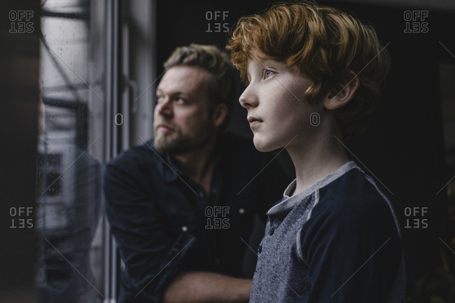 Boy and his father looking out of window on rainy day