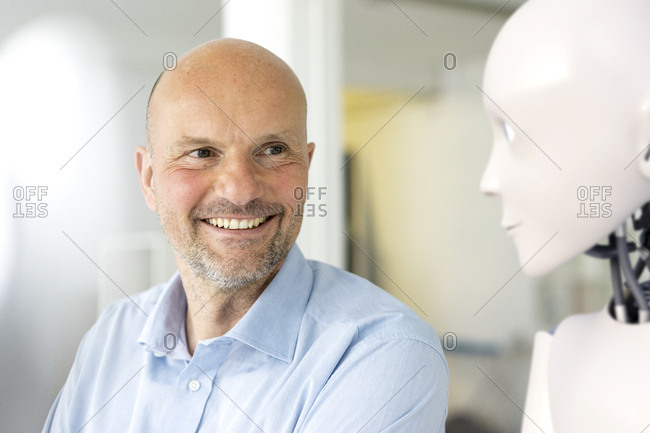 Portrait of smiling businessman looking at robot