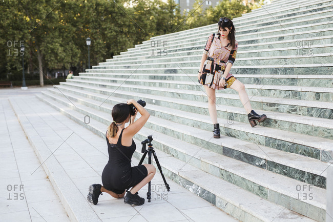 Young woman wearing patterned dress posing for a photo shoot on stairs