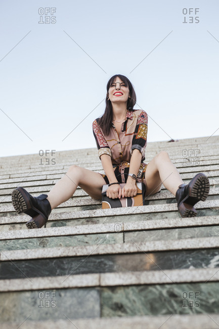 Young woman wearing patterned dress sitting on stairs
