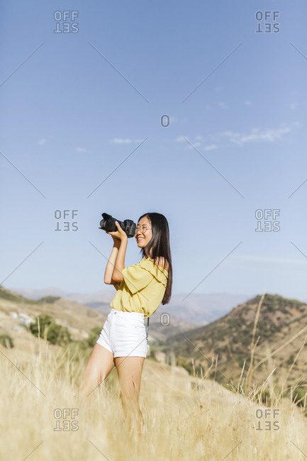 Young woman taking pictures in remote landscape- Granada- Spain