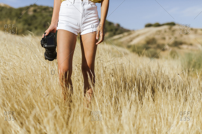 Low section of young woman with camera walking in remote landscape- Granada- Spain