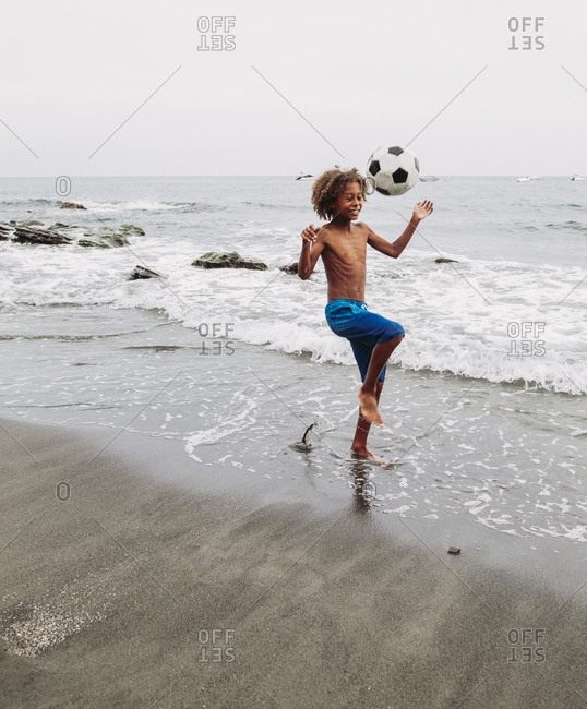 Boy playing with a football on the beach