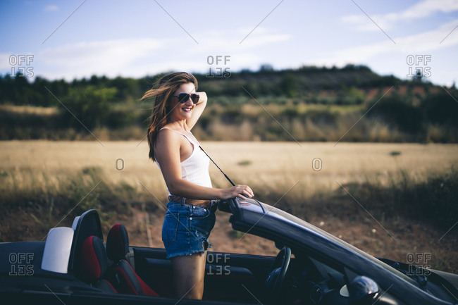 Woman standing in her convertible- looking at view
