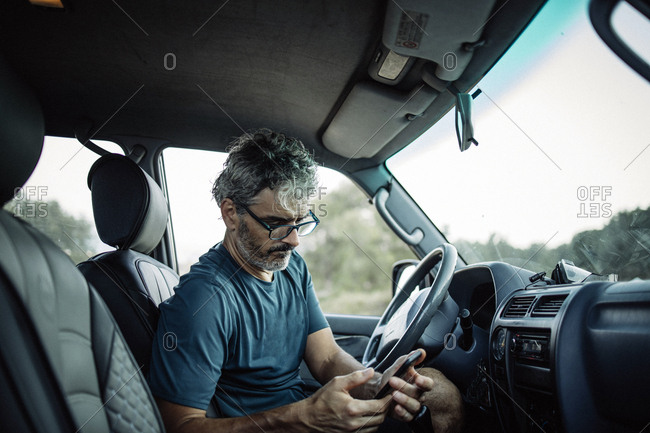 Mature man sitting in his off-road vehicle checking his smartphone