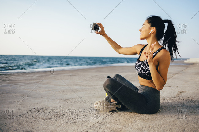 Woman using smartphone and taking a selfie- sitting on a pier