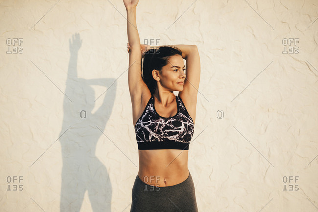 Young sportswoman stretching her arm