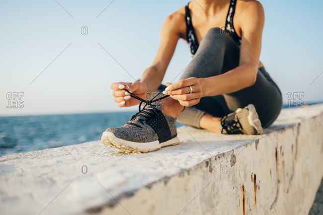Sportswoman sitting on a wall and tying running shoe