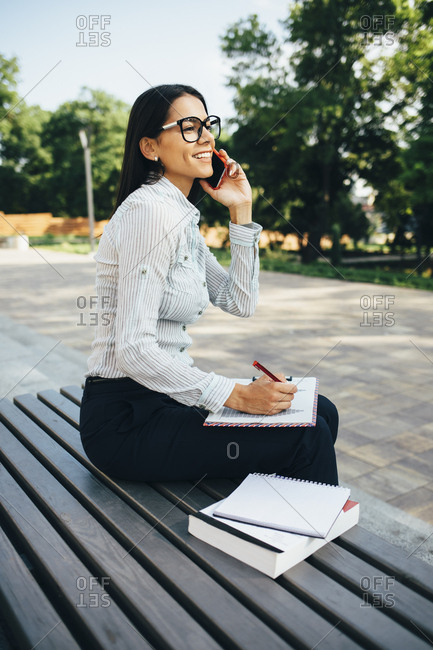 Young businesswoman sitting on a bench talking on cell phone and taking notes