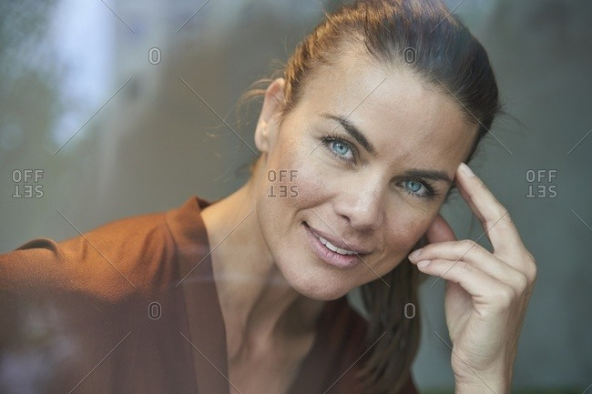 Portrait of smiling attractive woman behind windowpane