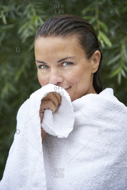 Portrait of woman with wet hair wrapped in a towel in nature