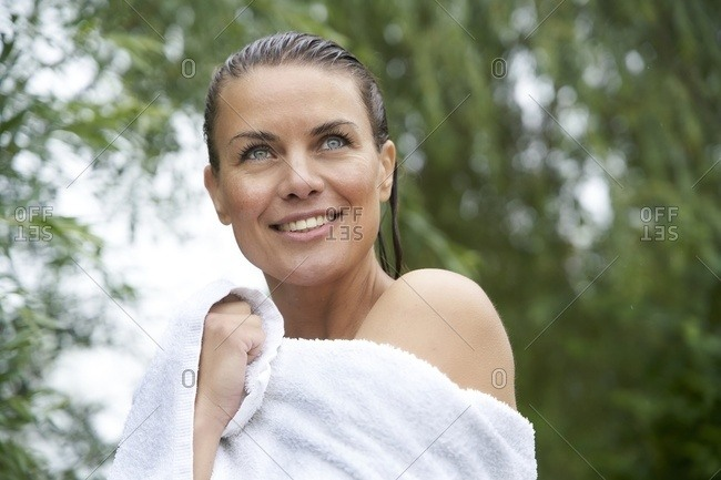 Portrait of smiling woman with wet hair wrapped in a towel in nature