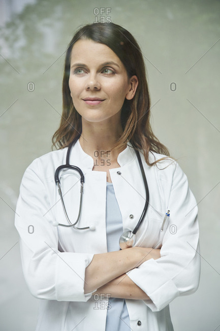 Portrait of confident female doctor behind windowpane