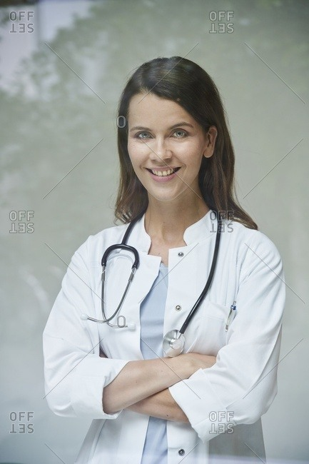 Portrait of smiling female doctor behind windowpane