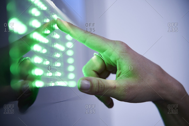 Detail of finger touching green led touchscreen