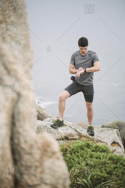 Trail runner standing in coastal landscape looking at his watch- Ferrol- Spain