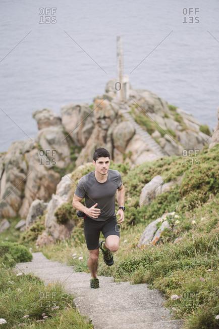 Trail runner on stairs in coastal landscape- Ferrol- Spain