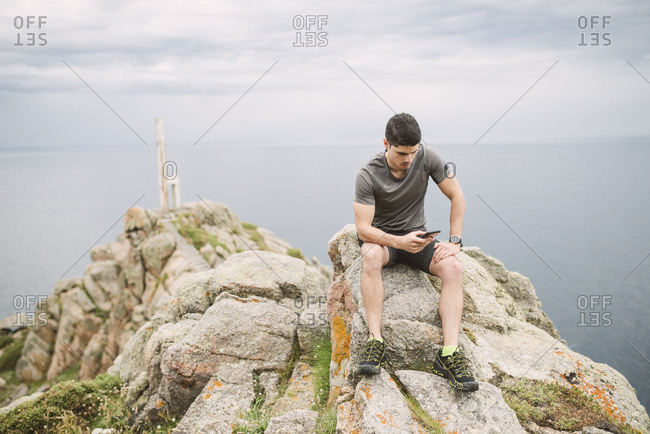 Trail runner sitting on a rock in coastal landscape looking at his cell phone- Ferrol- Spain