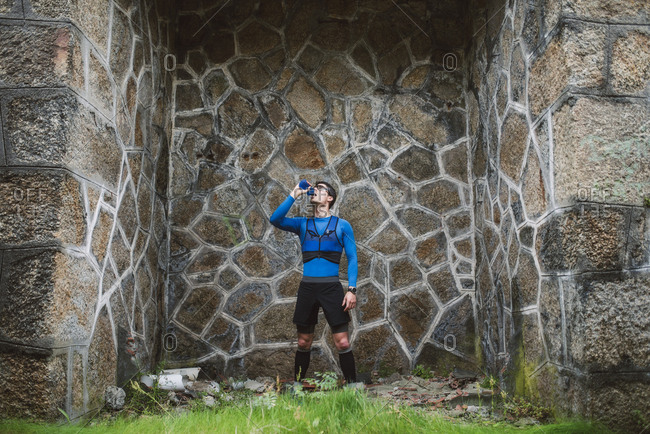 Trail runner standing at a wall drinking water