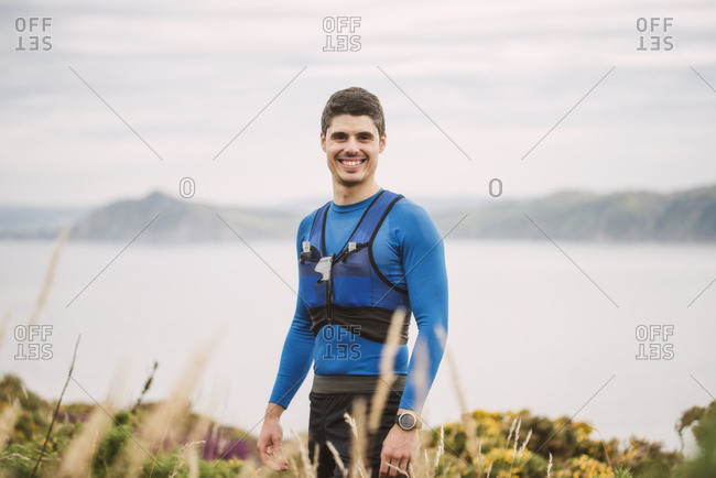 Portrait of smiling trail runner standing in the mountains- Ferrol- Spain