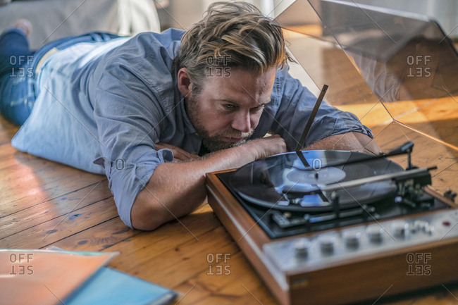 Man lying on the floor at home with a record player