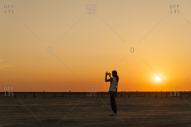Germany- Schleswig-Holstein- Sankt Peter-Ording- woman taking a picture on the beach at sunset