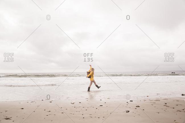 Woman wearing yellow rain jacket walking at the beach