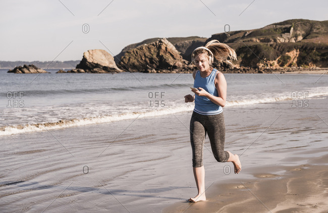 Female jogger at the beach- using smartphone and headphones