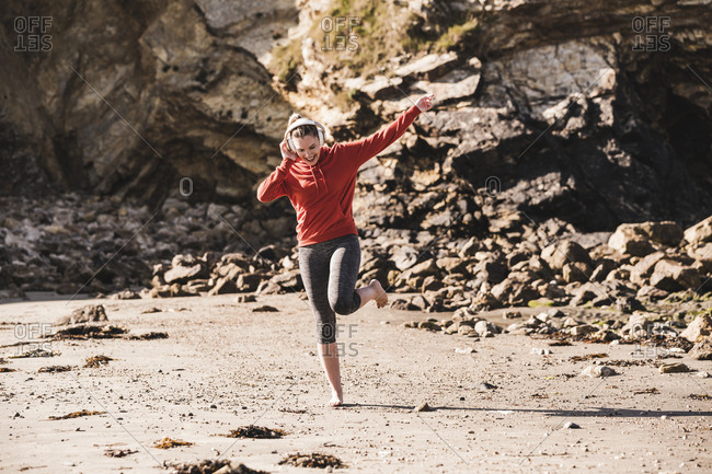 Female jogger dancing at the beach with headphones