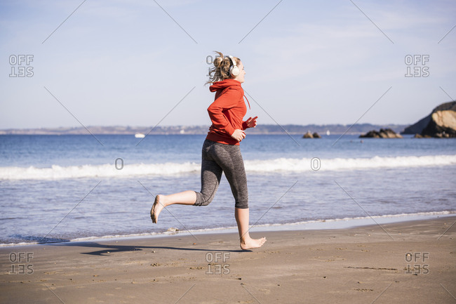 Female jogger at the beach with headphones