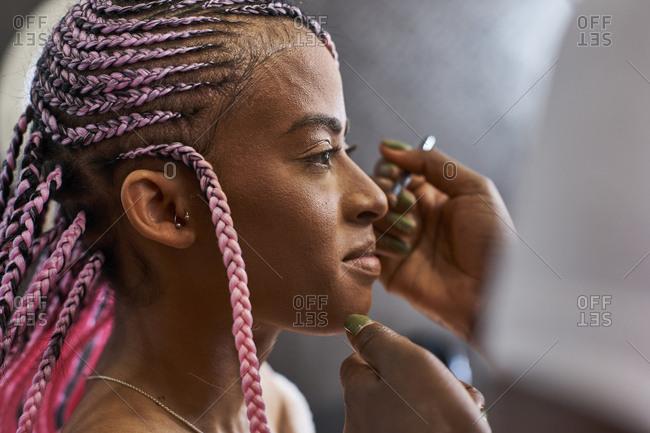 Visagiste applying makeup on young woman's face