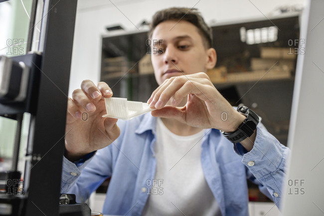 Student setting up 3D printer- using laptop