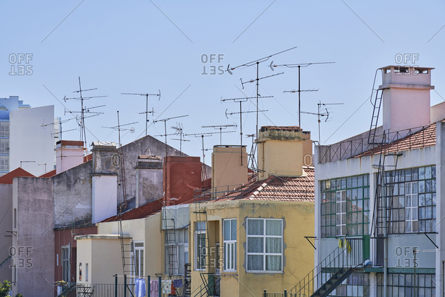 View of colorful neighboring apartment buildings with antennas in Lisbon, Portugal