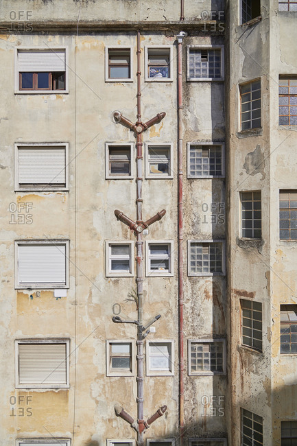 Lisbon, Portugal - September 6, 2019: Facade of old apartment building with plumbing pipes on wall