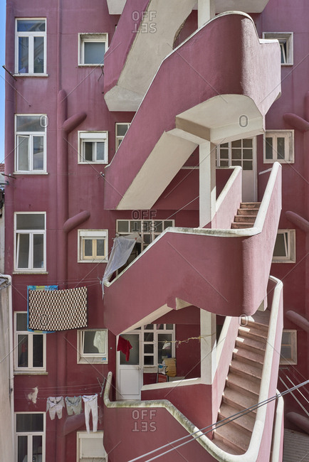 Fire escape on a dark pink apartment building in the city of Lisbon, Portugal