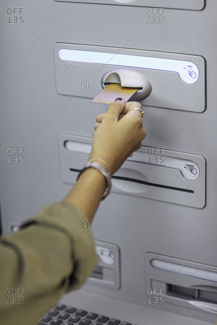 Hands of a young girl taking out money at an ATM