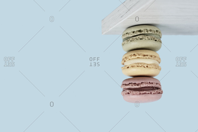 A pile of delicious macarons of hanging upside down from a white wooden board