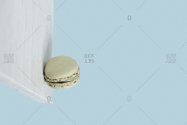 A delicious green macaron stuck on a vertical white wooden board