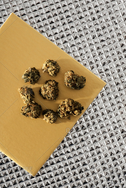 High angle view of some marihuana buds on a yellow surface