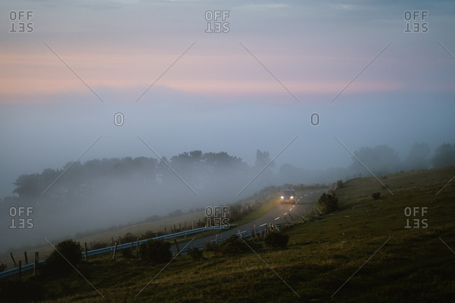 Gipuzkoa, Spain - September 13, 2019: Camper van driving through foggy road by the ocean during sunset