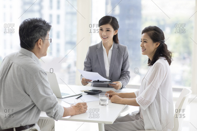 Happy mature Chinese couple talking with financial advisor at office