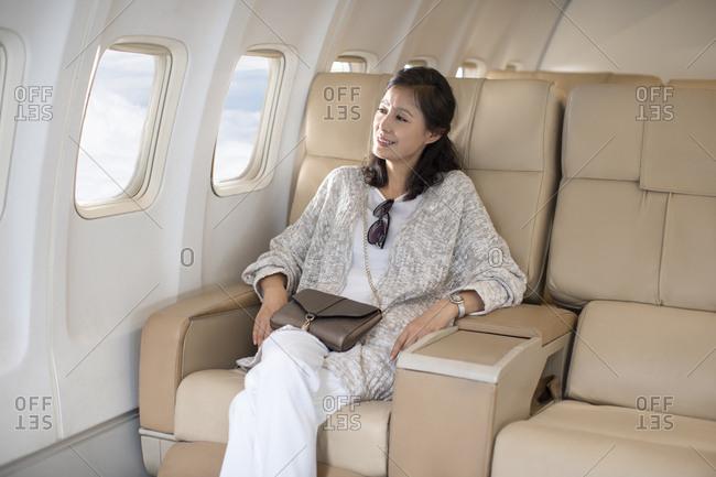 Mature Chinese woman traveling on plane
