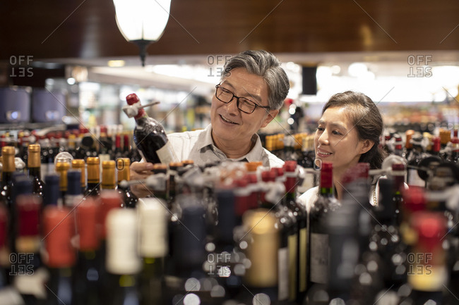 Mature Chinese couple choosing wine in supermarket