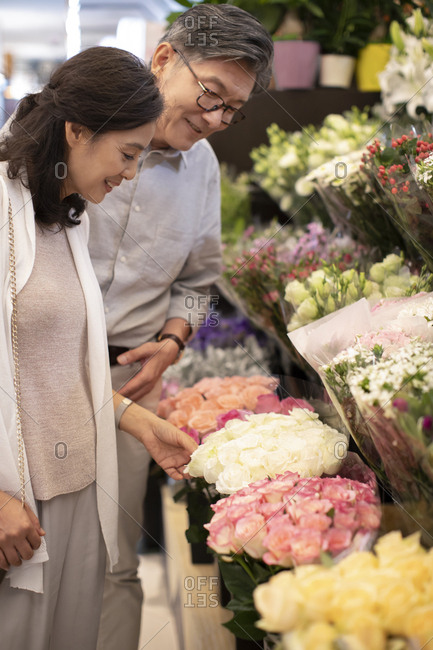Mature Chinese couple buying flowers in flower shop