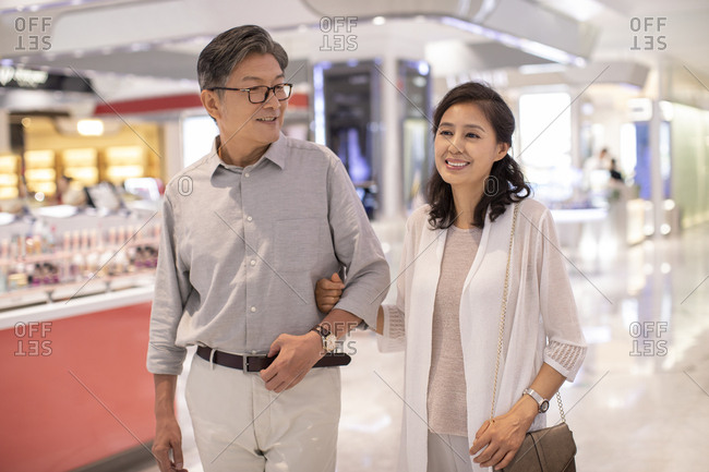 Mature Chinese couple shopping in shopping mall