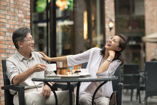 Mature Chinese couple having afternoon tea in coffee shop