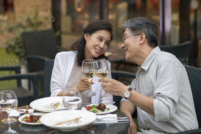 Mature Chinese couple toasting at restaurant
