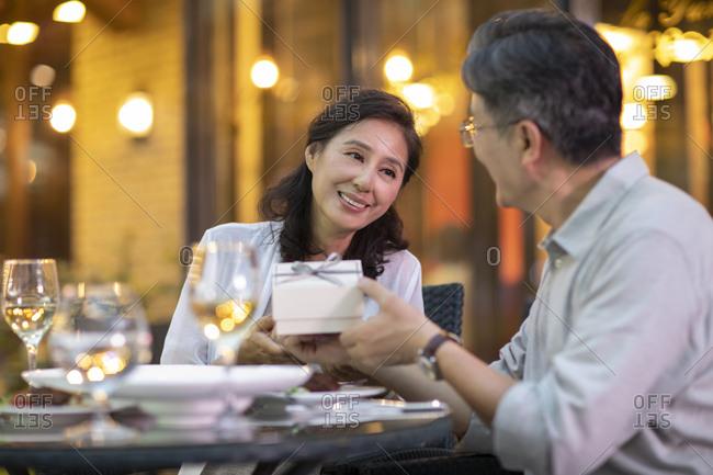 Mature Chinese couple celebrating wedding anniversary at restaurant