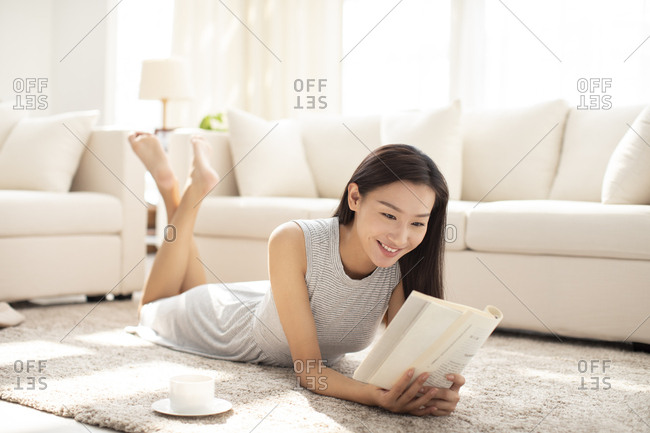 Young Chinese woman reading book in living room