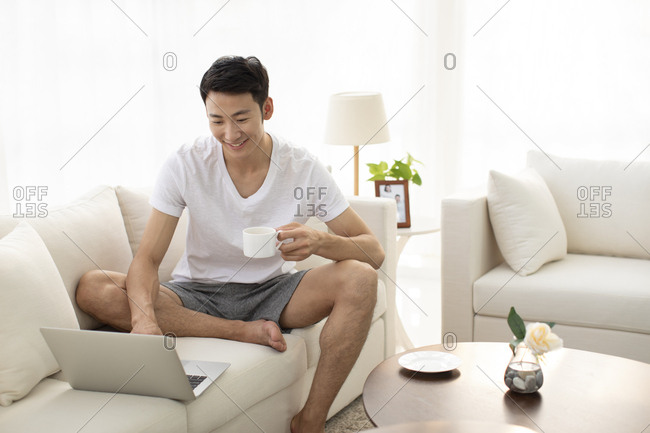 Young Chinese man using laptop in living room